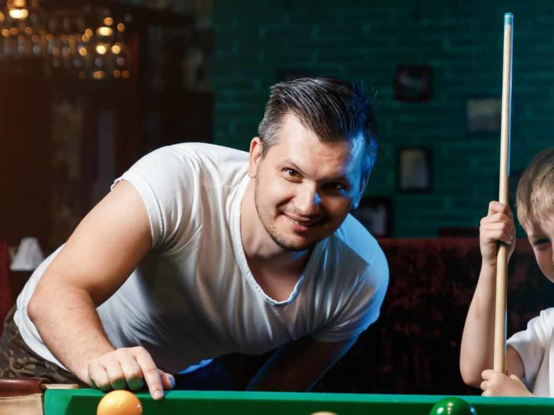 A dad and his son having a game of pool together