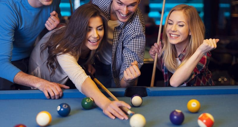 Friends cheering while their friend aiming for billiards ball