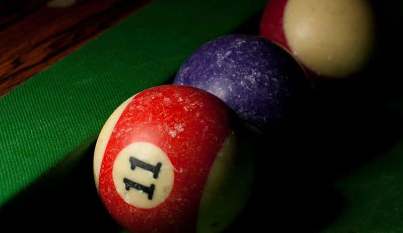 Well loved snooker balls lined up on the pool table