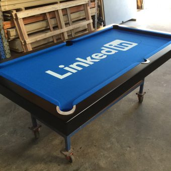 A custom pool table with the linkedin logo in the felt.