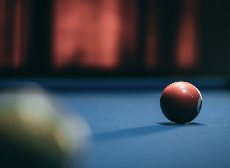 Blue pool table felt with a red ball rolling towards it.